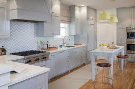 spacious transitional kitchen with gray cabinetry chevron backsplash and eat in island with marble countertop spacious eat kitchen