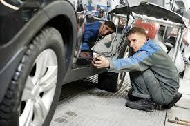 auto repairman worker in automotive industry examining car body auto repairman worker in automotive industry examining car body