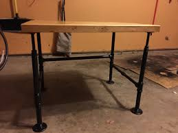 the next day i mounted the 12 floor flanges on the bottom of the table top then threaded the threaded rods in then i took the nuts screwed them on the black iron pipe table