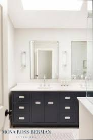 bathroom features gray shaker vanity: white and black bathroom features a skylight over a black double vanity adorned with vintage style pulls topped with white quartz fitted with round his and