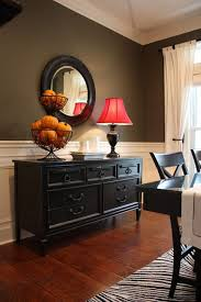 a black sideboard buffet table is a striking contrast to the dark color wall and charming pernk dining room