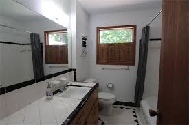 the fuul bathroom offers a spacious vanity and showertub combination and large window with shutters allowing natural light to fill the room while allowing natural light fill