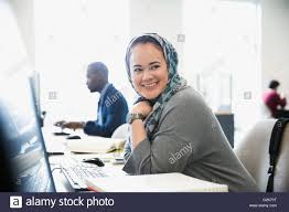 smiling college student in hijab researching at computer in smiling college student in hijab researching at computer in library