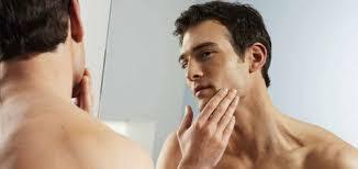 Shirtless man examining his face skin in the mirror