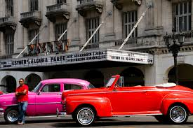 havana a photo essay a man stands next to his classic pink car itself sitting parked next to an