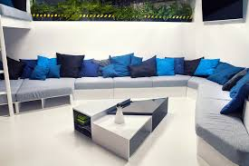 wonderful modern office design with white pipes exposed large couch with throw pillows in blue blue office room design