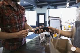 visual merchandising associate career profile man paying credit card reader in shop