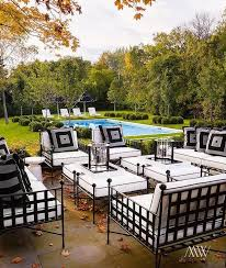 chic patio features wrought iron sofas chairs and ottomans covered in black and white cushions black wrought iron outdoor furniture