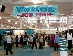 the psychological price of job loss the why files dozens of people mill around booths at a convention center sign hangs from ceiling
