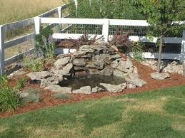 diy patio pond: small diy ponds with waterfall and stone border in the corner backyard