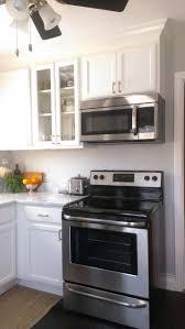 glass kitchen backsplash carrera marble small kitchen white cabinets carrara marble countertop dark floor stai