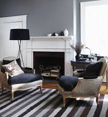 chic gray living room with gray walls paint color striped gray rug gray linen bergere chairs with navy blue velvet cushions black tripod floor lamp blue grey paint colors view
