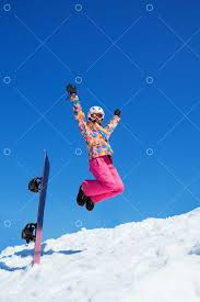 Happy woman with <b>snowboard jumping</b> in snow in mountains on ...