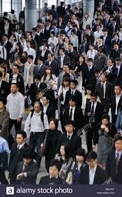crowd of commuters walking to work during morning rush hour in crowd of commuters walking to work during morning rush hour in railway station in tokyo