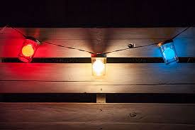 hang red white and blue patio string lights across a rustic white pallet during memorial patriotic mason jar blue mason jar string lights