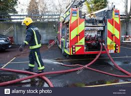 fire fighter training stock photos fire fighter training stock london fire brigade station training session a fire fighter connects the hoses to the