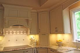 kraftmaid cabinetry in white finish with a brookfield door style a bhsld standard wall mount liner range hood under cabinet ligthing granite countertops cabinet lighting custom