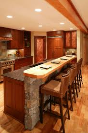 island comprised of stone wall and rich wood paneling matching the cabinetry throughout this kitchen center island lighting