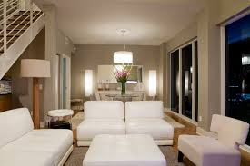 cozy neutral toned living room features an array of plush armless seating around a white beautiful small livingroom