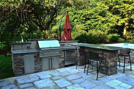 patio outdoor stone kitchen bar: with a flourishing natural backdrop the outdoor kitchen bar and hot tub fit seamless into the surroundings using natural stone and granite countertops