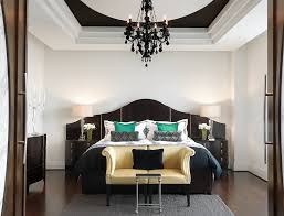 gorgeous chandelier inside black and white bedroom with wide bed and brown sofa on grey carpet black and white bedroom furniture
