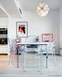 this ultra modern room is equipped with translucent dining room chairs and matching neon sight there is an amazing hanging lamp that reminds us of amazing hanging dining room
