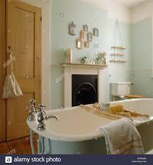 washstand bathroom pine: roll top bath with wooden bath rack in pale green bathroom with pine cupboard