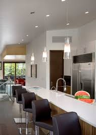 led kitchen pendant lighting above raised breakfast bar with white quartz countertops nearby swivel counter stools breakfast bar lighting