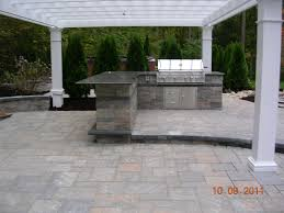 patio outdoor stone kitchen bar: outdoor kitchen and bar with stainless steel grill and pergola set on a paver patio by