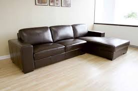 living room with bed: simple living room with dark brown sectional leather couch ikea and light brown wooden flooring