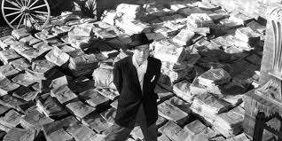 the best movies about politics page of  orson welles standing on stacks of newspapers in a scene from the film citizen kane