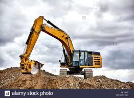 jobsite stock photos jobsite stock images alamy construction industry heavy equipment excavator moving gravel at jobsite quarry stormy skies stock image