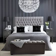 hotel style furniture. black striped wall upholstered bed with headboard bedside tables and lights a hotel style furniture