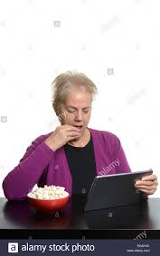 senior person holding ipad stock photos senior person holding middle aged w using a tablet computer while eating popcorn at home stock image