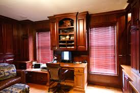 one wall of a clients home office features bookshelves cabinet storage flat screen tv with surround sound custom built in desk and floor to ceiling cherry custom home office desk