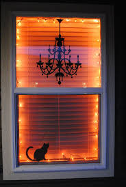 love halloween window decor: i love this halloween window decor idea with orange lights and black silhouettes its classy and simple she used a chandelier decal from target and a