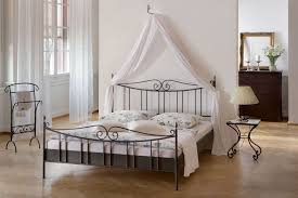 smokey gray wrought iron bed frames with white curtain above placed on brown herringbone hardwood floor bedroom endearing rod iron