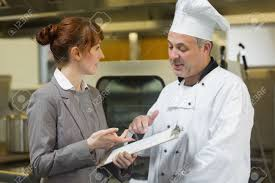 young female manager talking to the head cook standing in a stock photo young female manager talking to the head cook standing in a professional kitchen