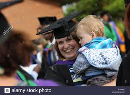 smiling mother holding her child after graduating from university stock photo smiling mother holding her child after graduating from university