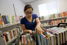 how to happy popular authors by genre pima county a library page is busy shelving books at sahuarita library