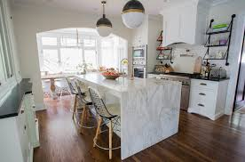 calacatta marble kitchen waterfall: stunning kitchen with center island boasting a waterfall edge calcutta gold marble counter which frames a farm sink and gooseneck bridge faucet across from