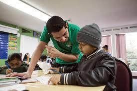 join tfa teach for america teacher leaning over desk to help student