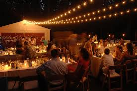 night photo of backyard wedding reception in driveway featuring candles and cafe lights backyard wedding ideas