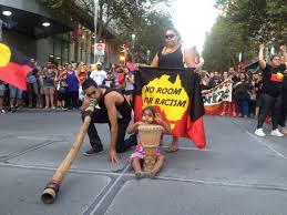 racism towards indigenous australians  reporting the good with the bada man plays the didgeridoo as protesters in melbourne rally against the planned closure of up to remote communities in western australia