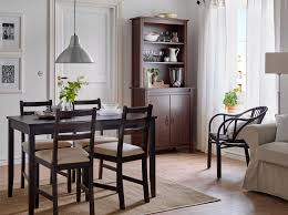 dining room sets ikea: a dining room with a black brown dining table and chairs with beige seat covers