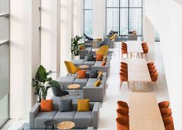 mustard yellow and rust orange sat upon custom designed carpets with a geometric print a strip of blonde wood meeting tables separates the lounge blonde wood office