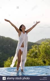 <b>Woman</b>, <b>stand</b> young, <b>summer dress</b>, pool margin, arms rised Stock ...