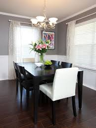 dining room khaki tone: chair rail molding divides two toned walls in this neutral dining room sheer curtains
