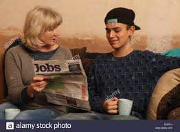 teenager grandmother looking at newspaper for jobs model stock photo teenager grandmother looking at newspaper for jobs model released