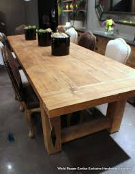long wood dining table: long rectangular solid wood dining table have  dining chairs that also have  black flowers vase on the table top above the cement floor for simple dining